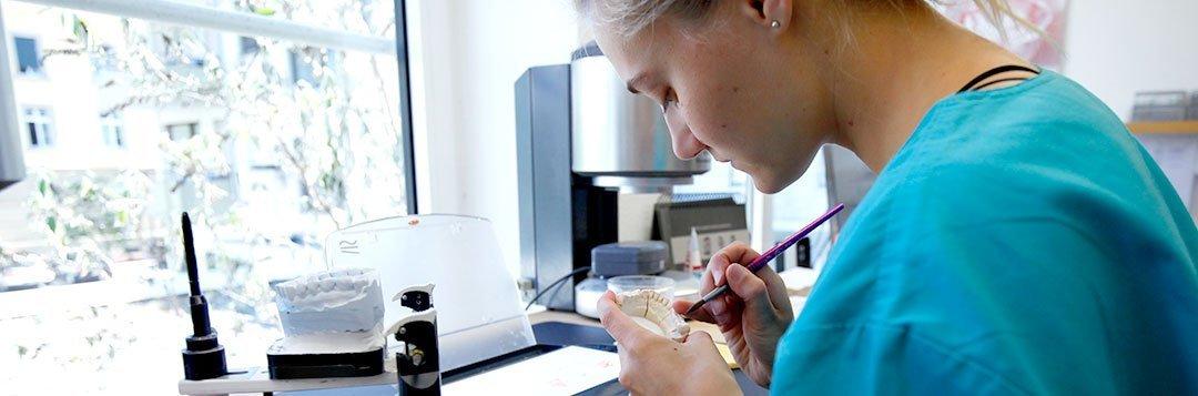 Zahntechnikerin im Labor beim erstellen eines Zahnersatzes