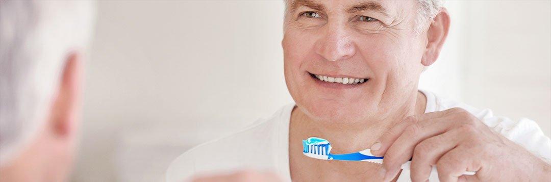 Mann bei der täglichen Zahnpflege seiner Zahnprothese
