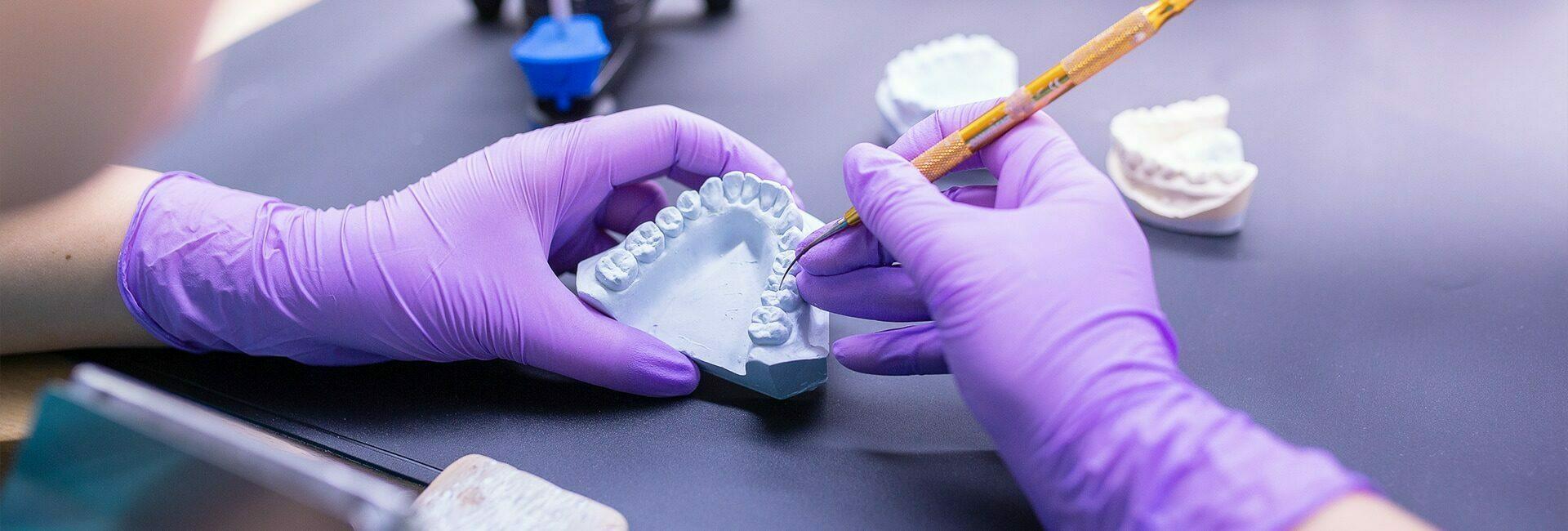 Zahntechnikerin beim Erstellen eines Zahnersatzes