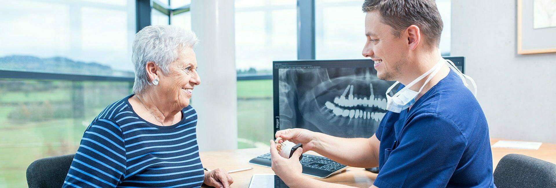 Zahnarzt erklärt Patientin die Implantationssysteme bei Zahnimplantaten