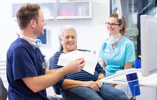 Zahnarzt bei einem Beratungsgespräch mit Patientin